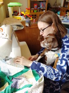 Photo: Karli sews a quilt on her sewing machine. A small dog sits in Karli's lap as she sews.