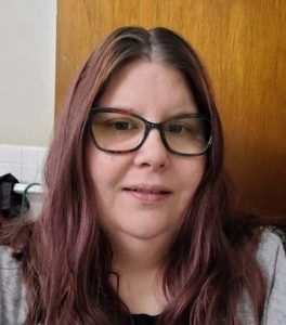 A picure of Katie. A white women with long reddish hair and glasses